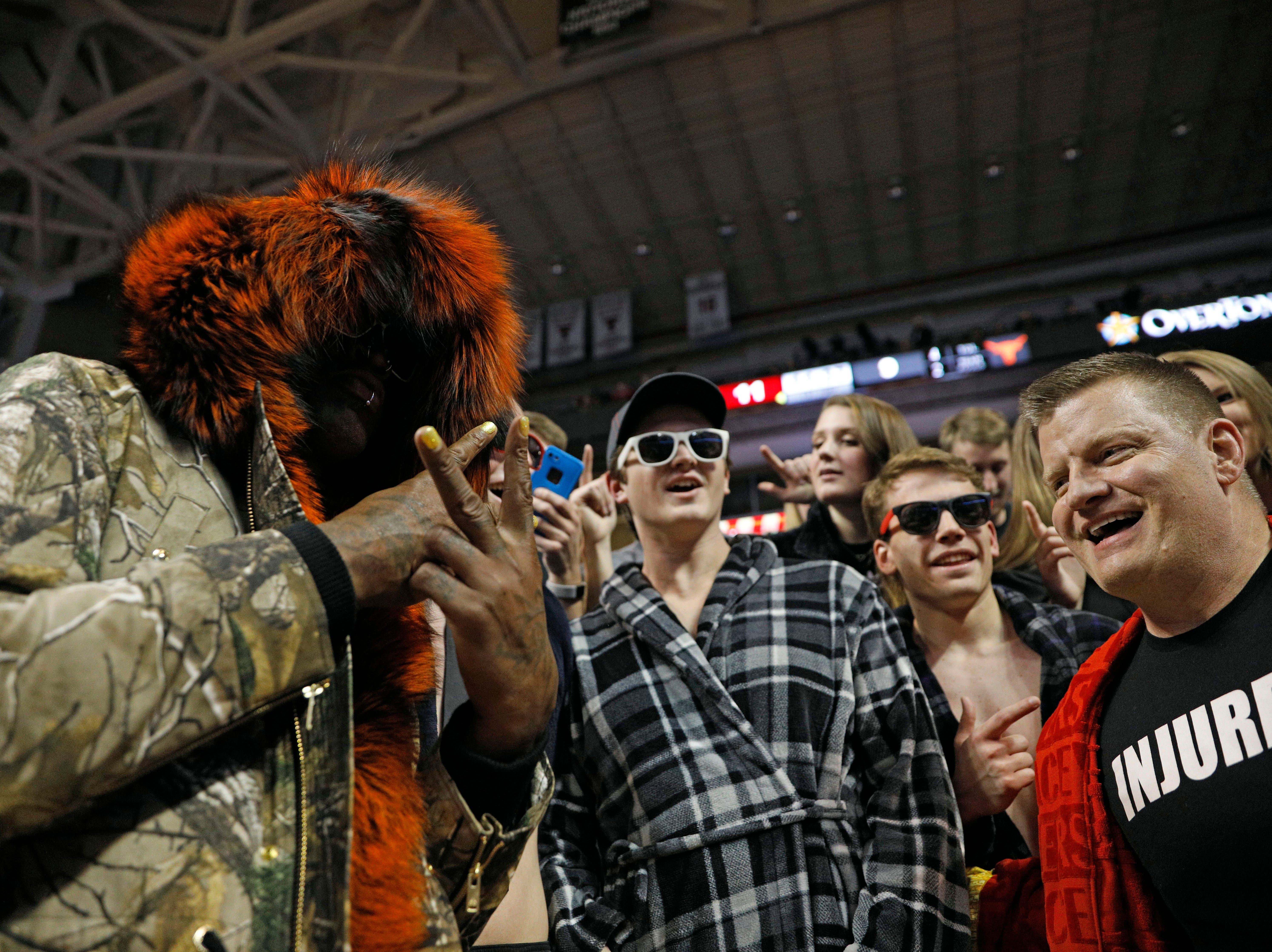 Dennis Rodman, left, cheers with Texas Tech fans during the first half of an NCAA college basketball game against Texas, Monday, March 4, 2019, in Lubbock, Texas. (AP Photo/Brad Tollefson)