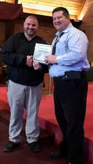 Chillicothe Correctional Institution Warden Tim Shoop presents Johnathan Johnson with the CCI Employee of the Year award for 2019.