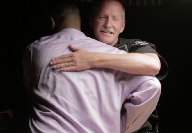 A Seattle police officer with the Law Enforcement Assisted Diversion program hugs a man who is back on his feet, working and healthy due to the program.