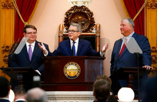 Ohio Governor Mike DeWine, center, speaks between Ohio Senate President Larry Obhof, left, and Ohio House Speaker Larry Householder during the Ohio State of the State address at the Ohio Statehouse in Columbus, Ohio, Tuesday, March 5, 2019. (AP Photo/Paul Vernon)