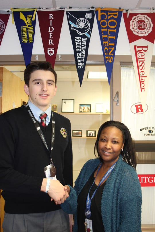 Shown here is Peter Gallo receiving a congratulatory handshake from his Guidance Counselor Shawanna Eugene for being named a National Merit Scholar Finalist.