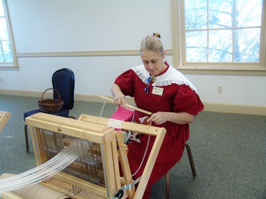 Stacie Stein prepares material on a loom for the previous weaving workshop in Roscoe Village.