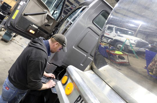 Mike Hothem runs a diagnostic on a truck at Precision Trucking in Fresno.