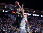 Winterset junior Easton Darling runs up a shot over Sergeant Bluff-Luton junior Daniel Wright in their Class 3A quarterfinal game during the 2019 Iowa high school boys state basketball tournament at Wells Fargo Arena in Des Moines.