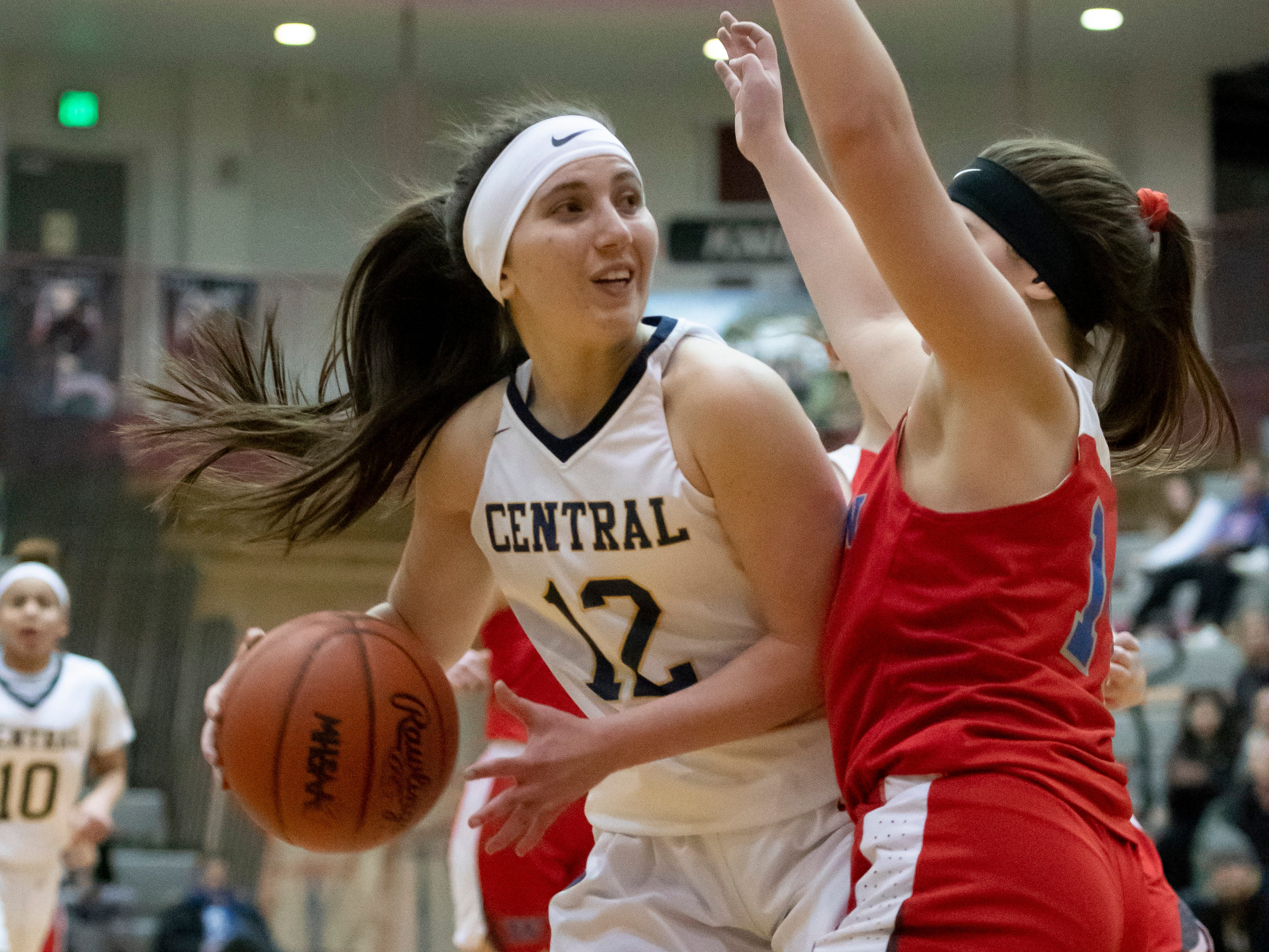 Walled Lake Central guard Angelina Haisha tries to get the ball past Walled Lake Western guard Olivia Warren during the first half.