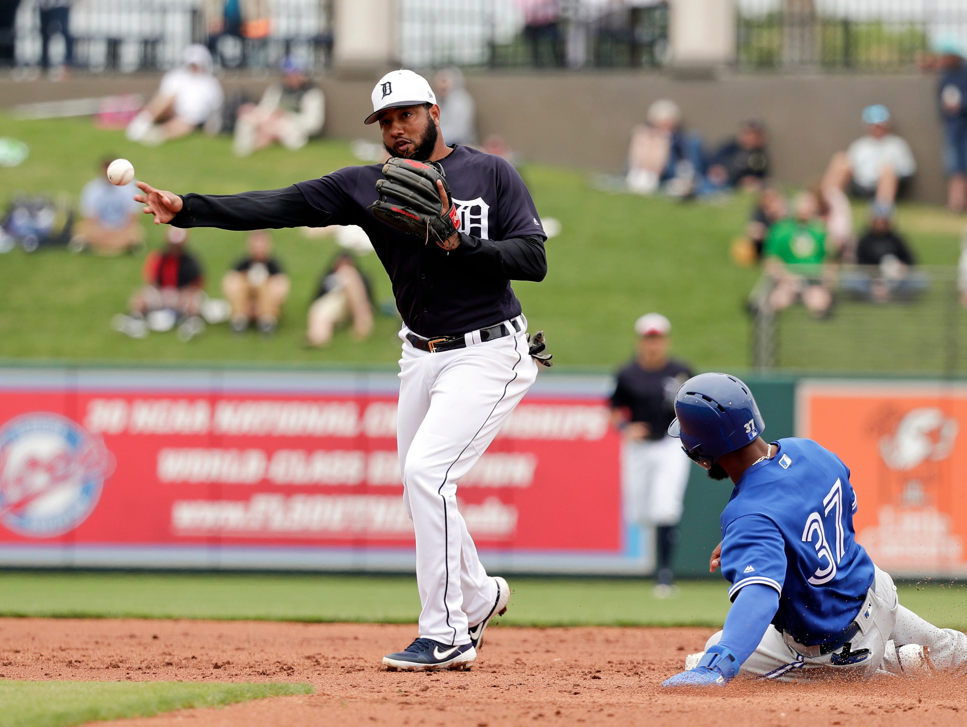 Detroit Tigers second baseman Ronny Rodriguez, left, throws to first for a double play after forcing Toronto Blue Jays right fielder Teoscar Hernandez (37) out at second during the third inning of a spring baseball exhibition game.