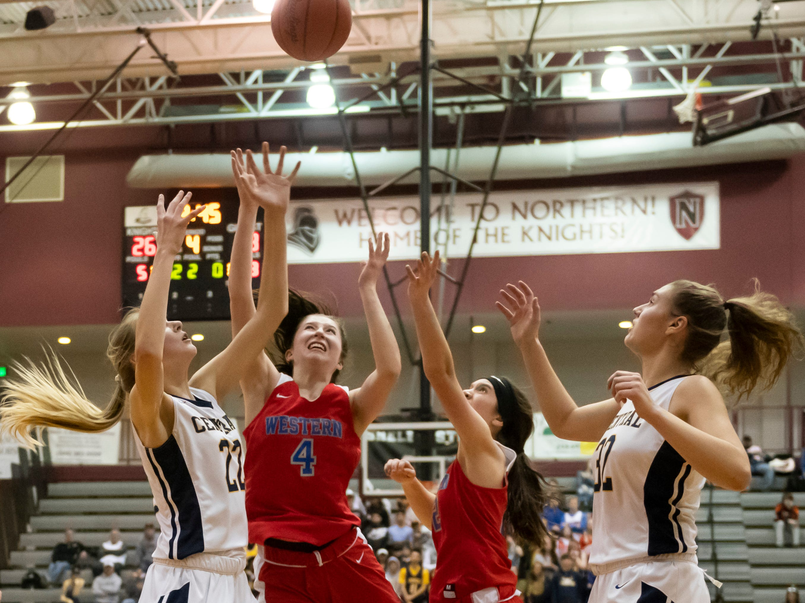 Walled Lake Western and Walled Lake Central battle for a rebound during the district 8 girls basketball district tournament at Walled Lake Northern high school, in Commerce Twp., March 4, 2019.