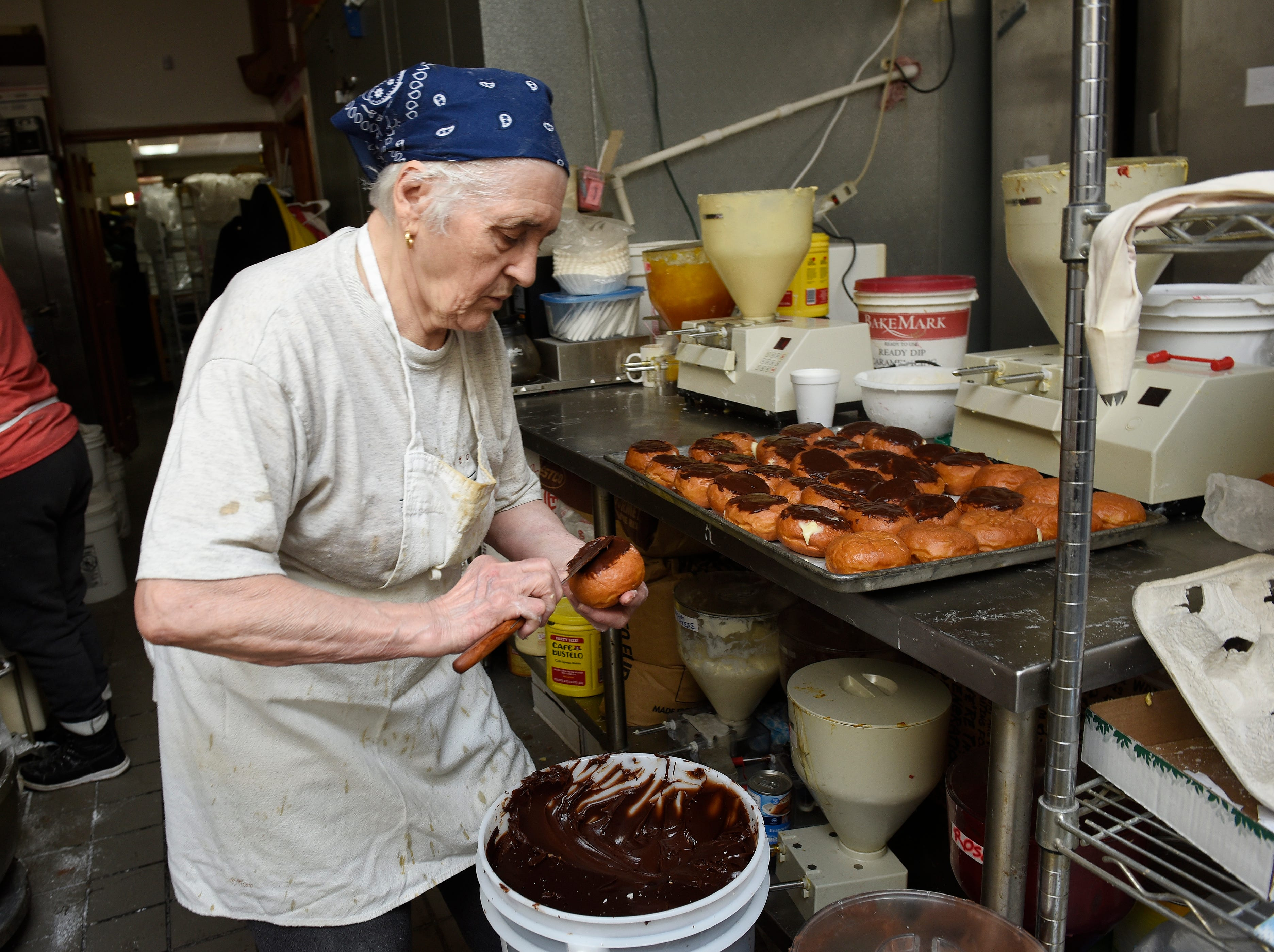 Ivanka Petrovic, co-owner of the bakery applies chocolate fudge on a Boston Cream paczek.