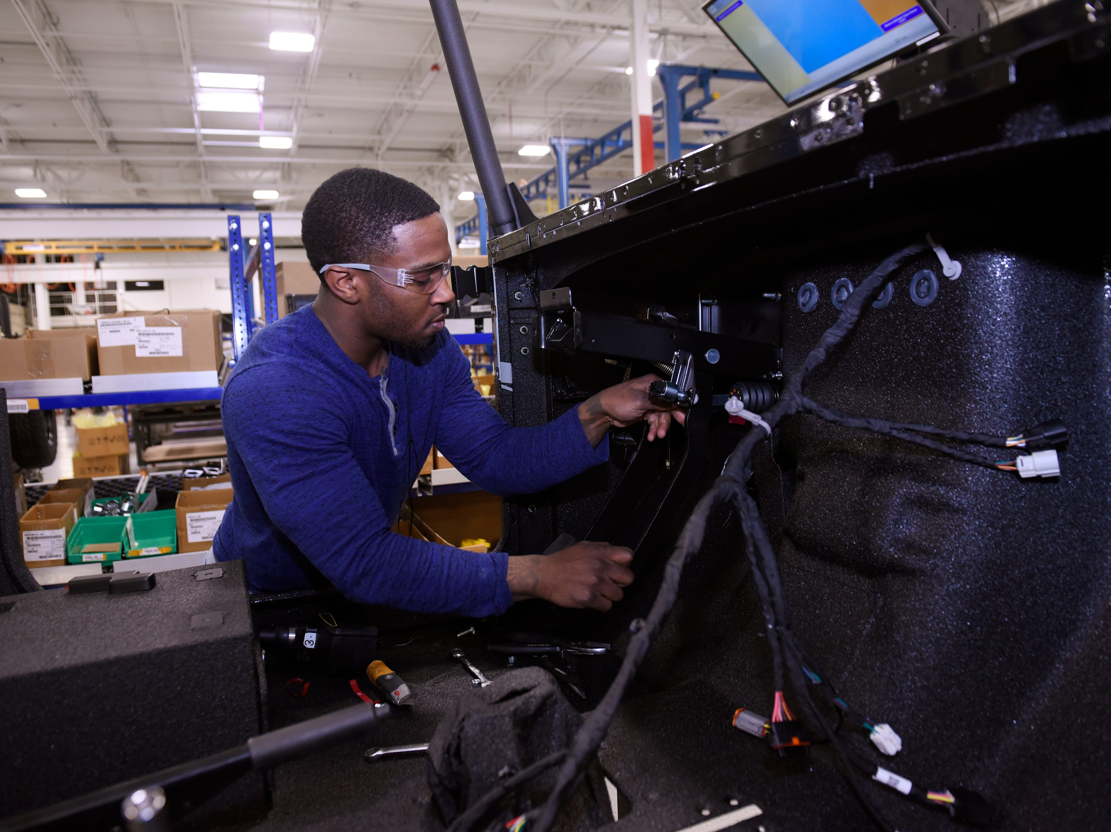 Jeremy Chambers, 27, installs gas and brake pedals during production at the Mahindra automotive plant in Auburn Hills, March 4, 2019.