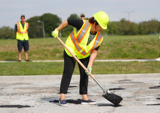 Michigan Democratic gubernatorial candidate Gretchen Whitmer fills a pothole during a campaign event in Southfield, Mich., Monday, Aug. 6, 2018. (AP Photo/Paul Sancya)