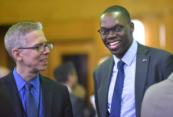 Michigan Department of Health and Human Services Director Robert Gordon, left, talks with Lt. Gov. Garlin Gilchrist before the meeting.