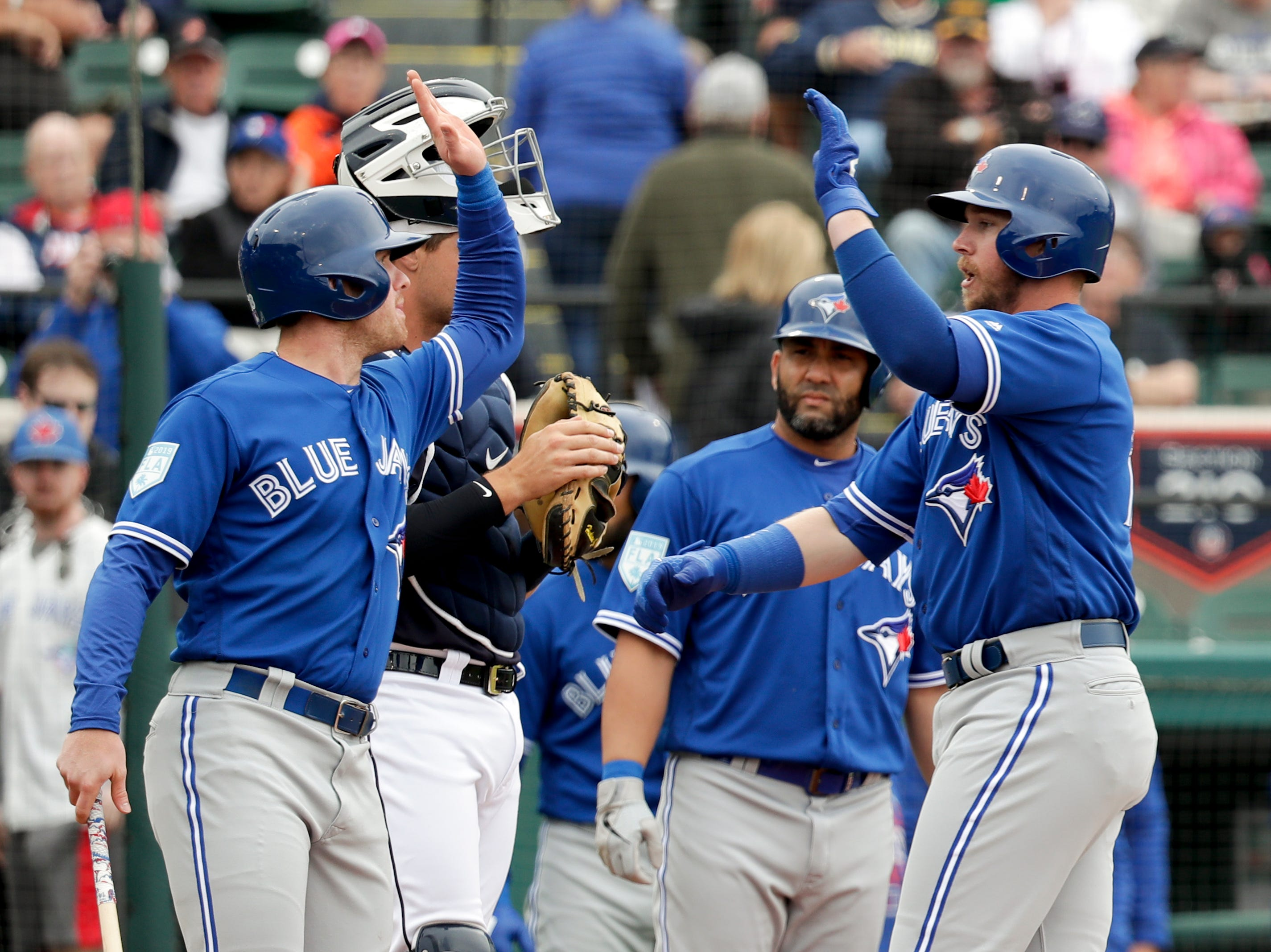 Toronto Blue Jays' Justin Smoak, right, high-fives teammate Billy McKinney after hitting a 3-run home in the first inning against the Detroit Tigers of a spring training baseball game, Tuesday, March 5, 2019, in Lakeland, Fla.