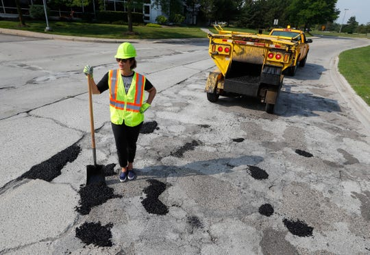 Then gubernatorial candidate Gretchen Whitmer fills a pothole during a campaign event Aug. 6. in Southfield.