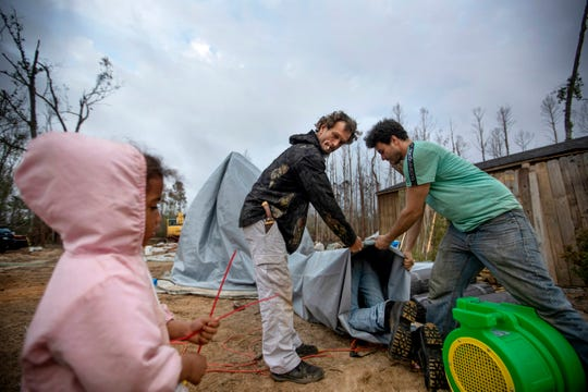 """Jeff Dunn, left, and Lance Gomez help construct a dome shelter in Diahnn """"Shelly"""" Summers' backyard for local residents left homeless from Hurricane Michael in Youngstown, Fla., Wednesday, Jan. 23, 2019."""