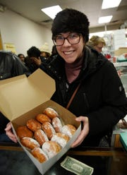 Erin Harris, 26, of Hamtramck, displays a dozen paczki she bought at  the New Martha Washington Bakery in Hamtramck for her work colleagues.