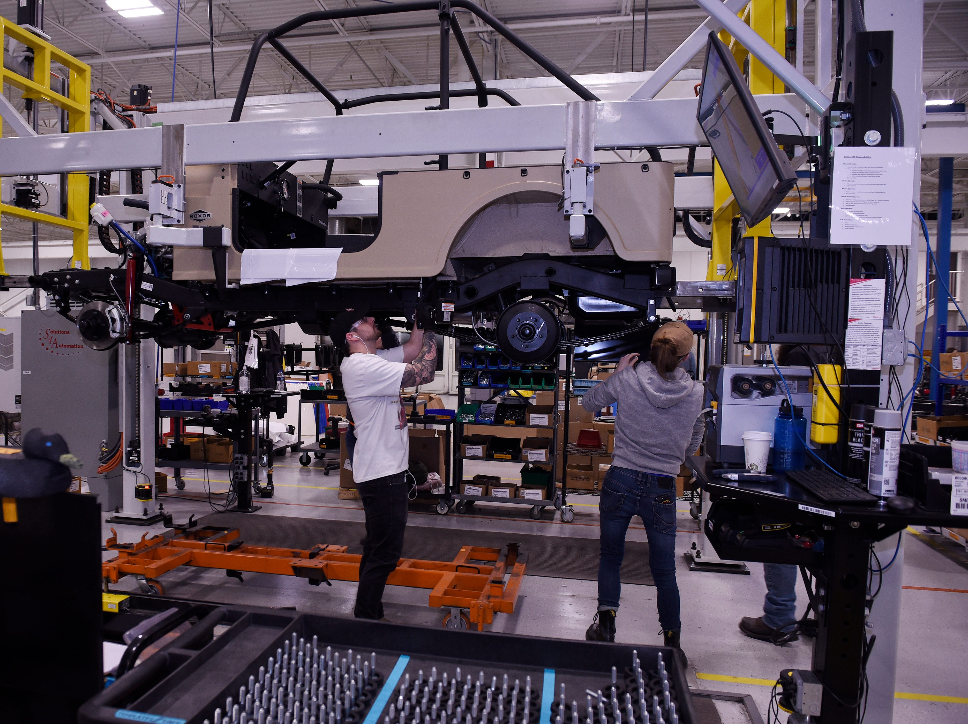 Dylan Christopher, 24, left, installs a chassis at the Mahindra automotive plant in Auburn Hills, March 4, 2019.