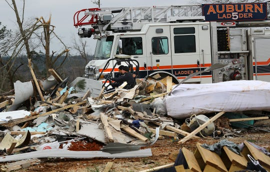 Rescue workers in a four wheeler pass by the wreckage of a home along Lee Road 38 after a Sunday night tornado on Monday, March 4, 2019, in Beauregard, Ala.
