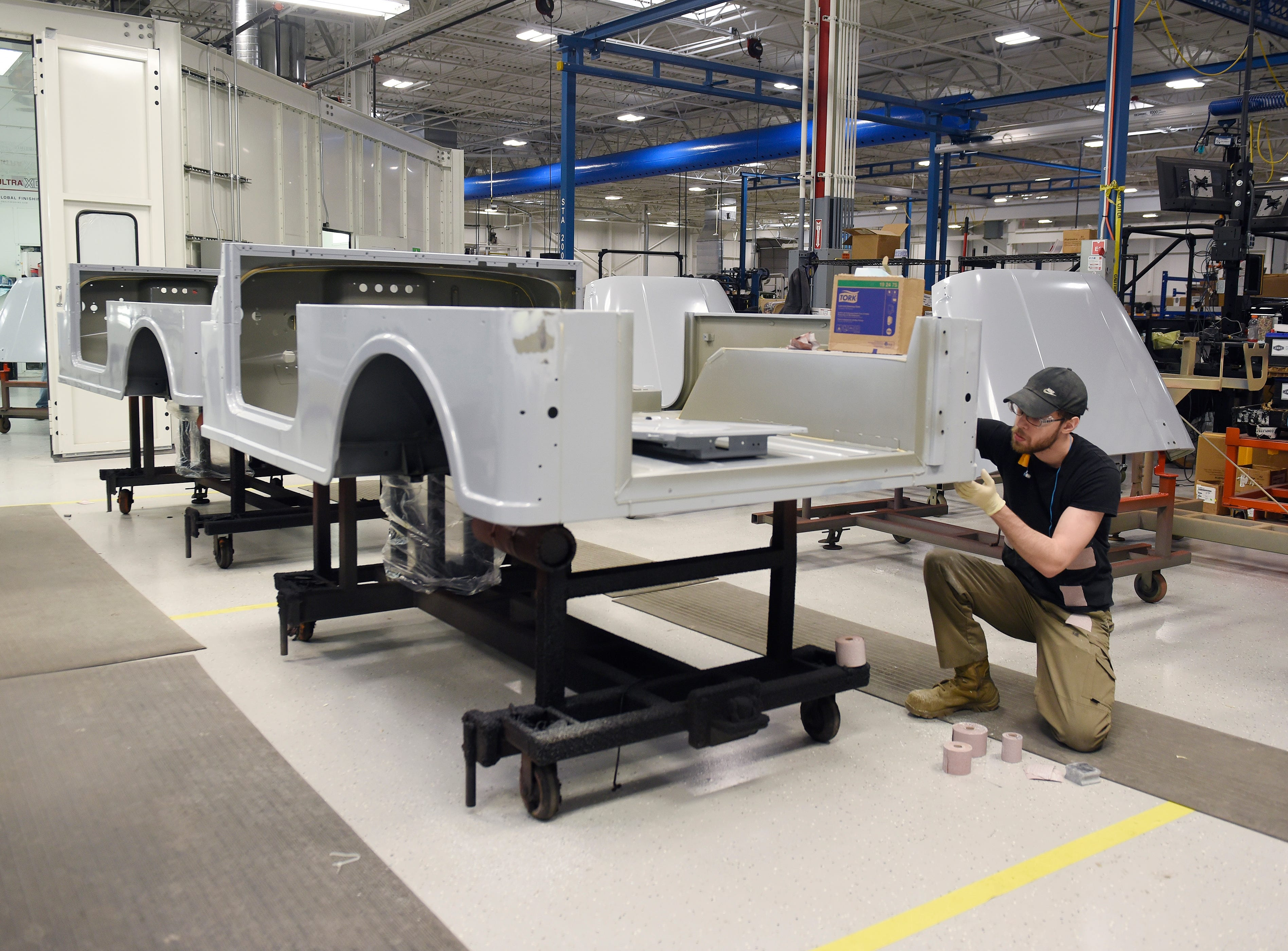 Christopher Pope, 26, sands a frame in preparation for painting at the Mahindra automotive plant in Auburn Hills, March 4, 2019.