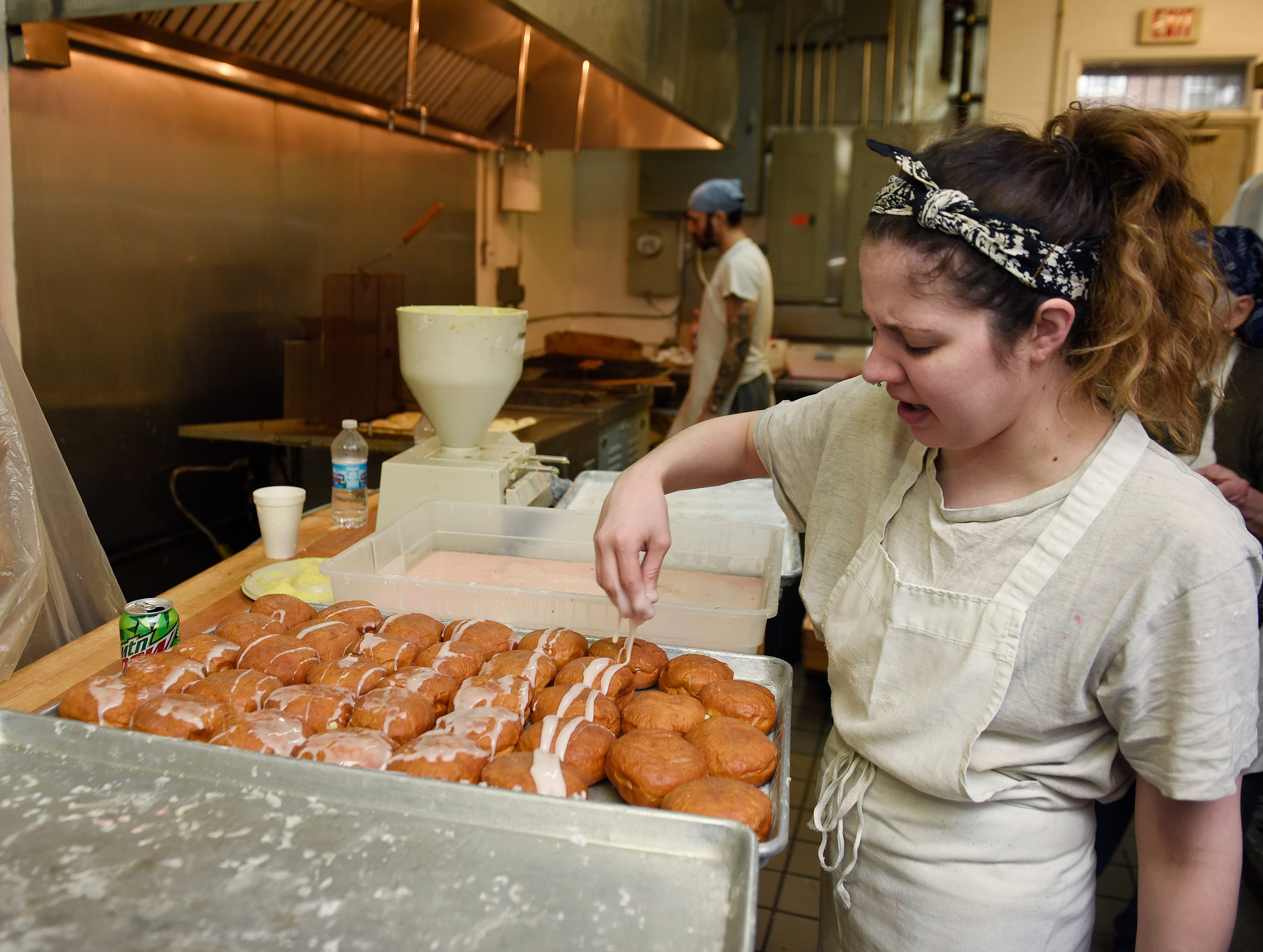 Petrisha Bakic, 28, applies glaze to a batch of bavarian cream paczki.