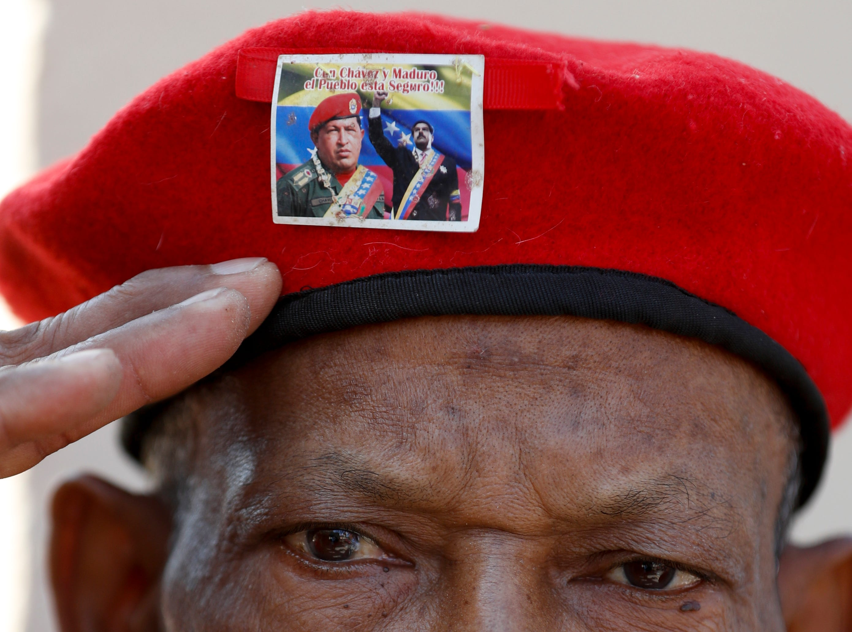 A man wearing the iconic red beret of Venezuela's late President Hugo Chavez, featuring a photo of current President Nicolas Maduro with Chavez, salutes as he waits to enter the Historic Military Museum to visit the leader's remains on the sixth anniversary of his death in Caracas, Venezuela, Tuesday, March 5, 2019.