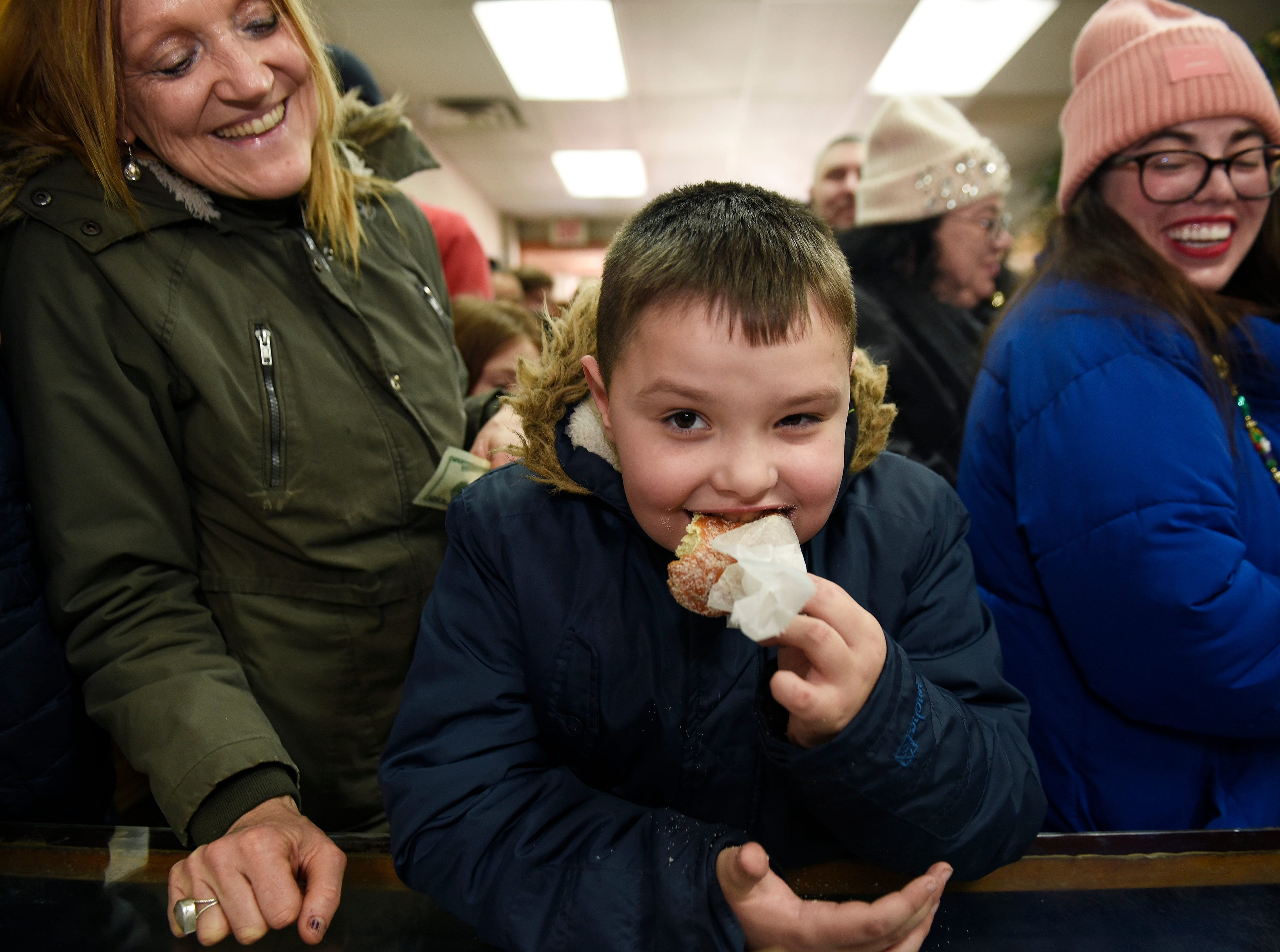 Landon Taylor, 8, of Flat Rock takes a bite of his plain sugar paczek as his grandmother Margaret Gonzalez, (l), and Melissa Schaf of Taylor looks on at New Martha Washington Bakery.