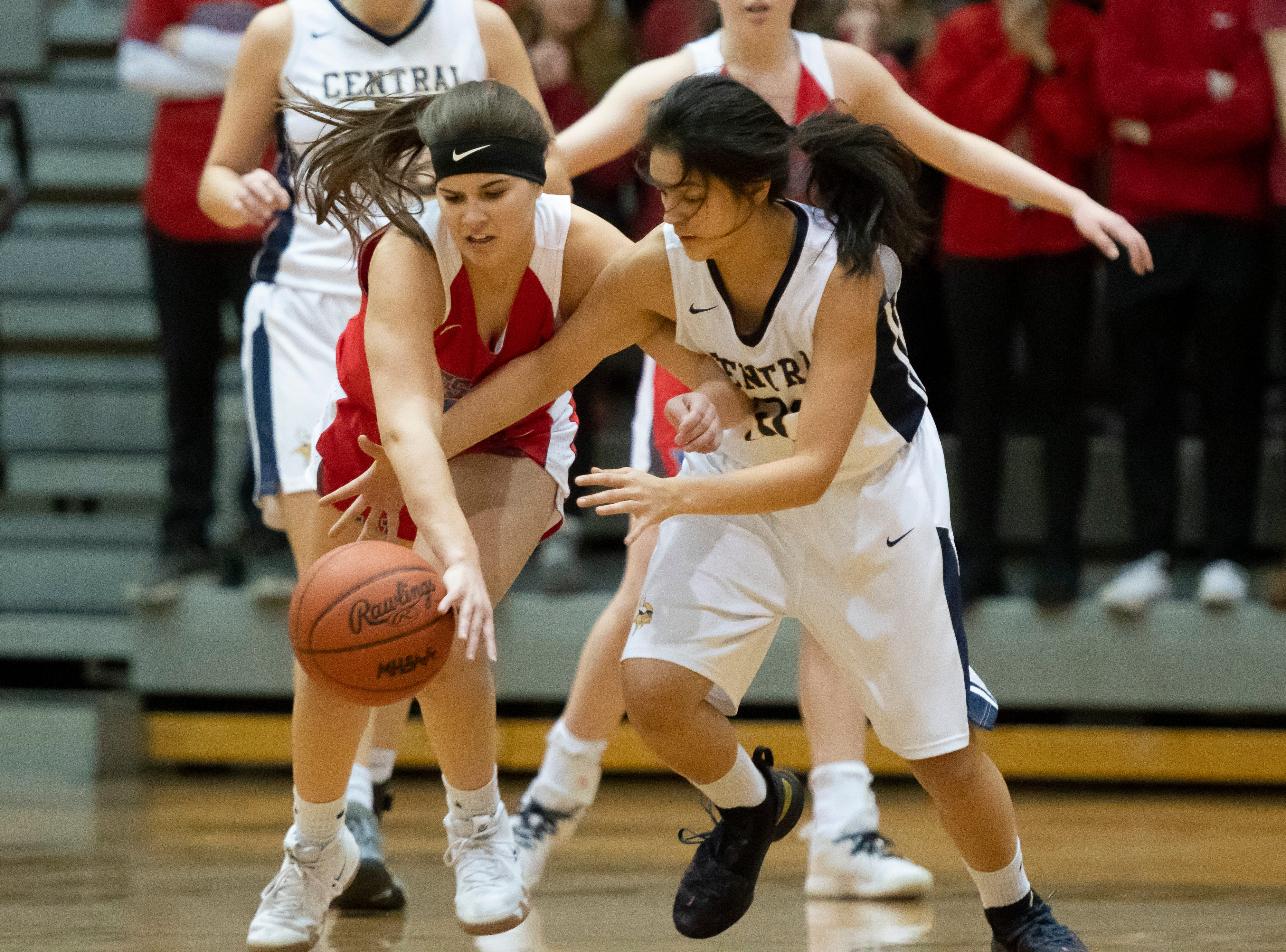 Walled Lake Western guard Olivia Warren, left, and Walled Lake Central guard Maria Teodoro battle for a loose ball in the first half. Western defeated Central 48-31 knocking their rival out of the state playoffs.
