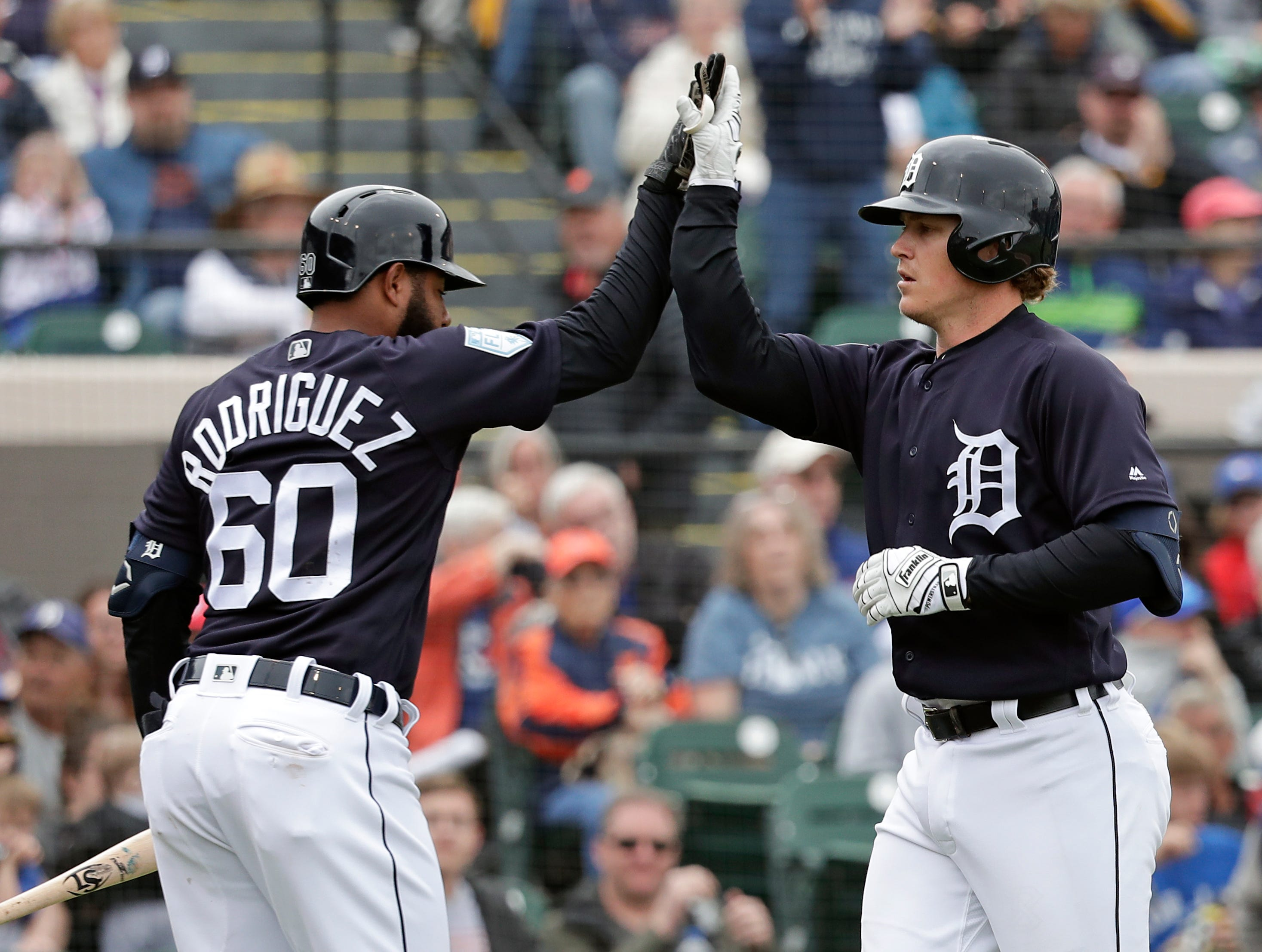Detroit Tigers' Brandon Dixon, right, gets a high-five from Ronny Rodriguez (60) as he heads to the dugout after hitting a solo home run in the fourth inning of a spring training baseball game against the Toronto Blue Jays, Tuesday, March 5, 2019, in Lakeland.