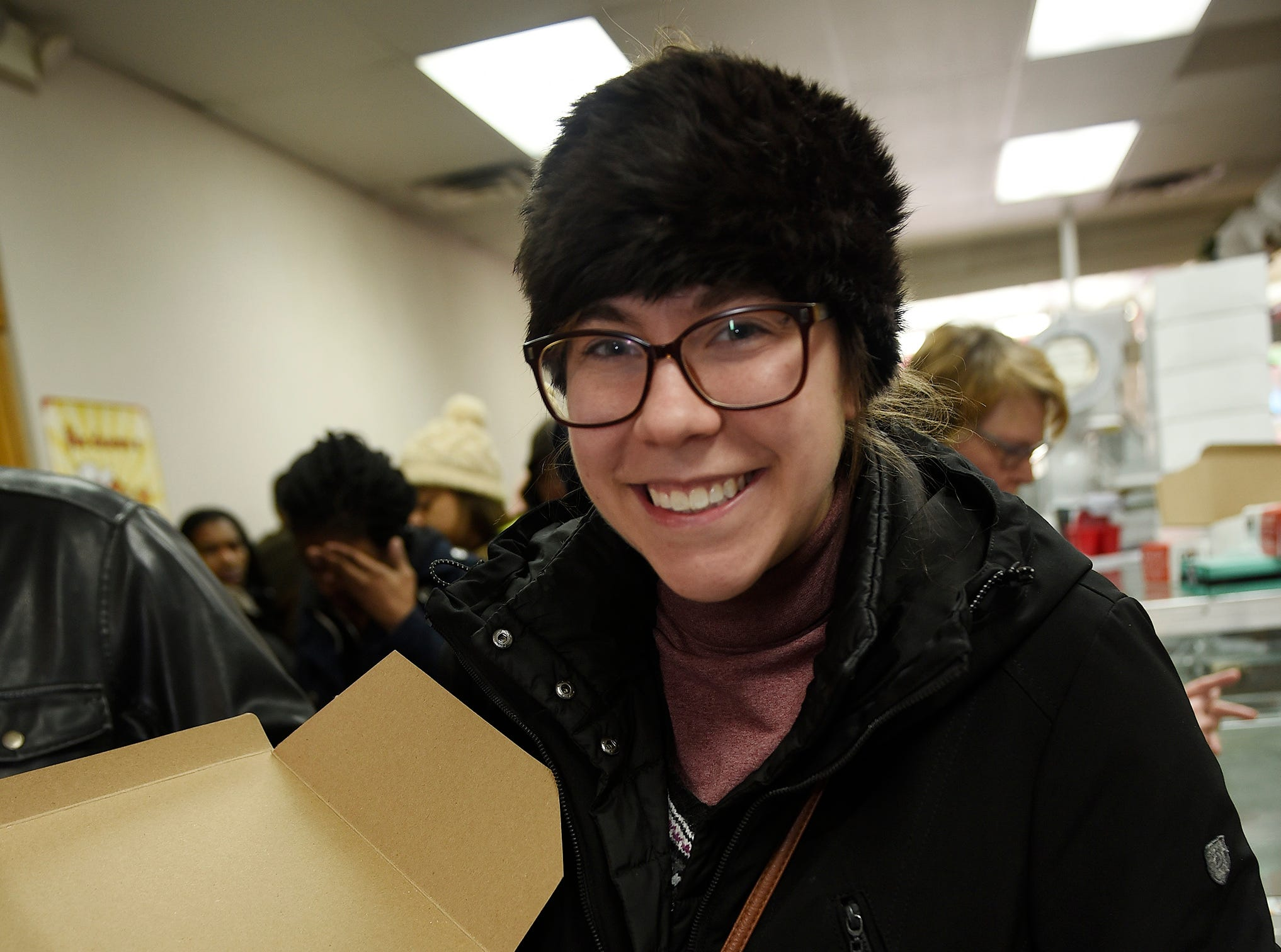 Erin Harris, 26, of Hamtramck displays a dozen of paczki that she will be taking to work for her colleagues.