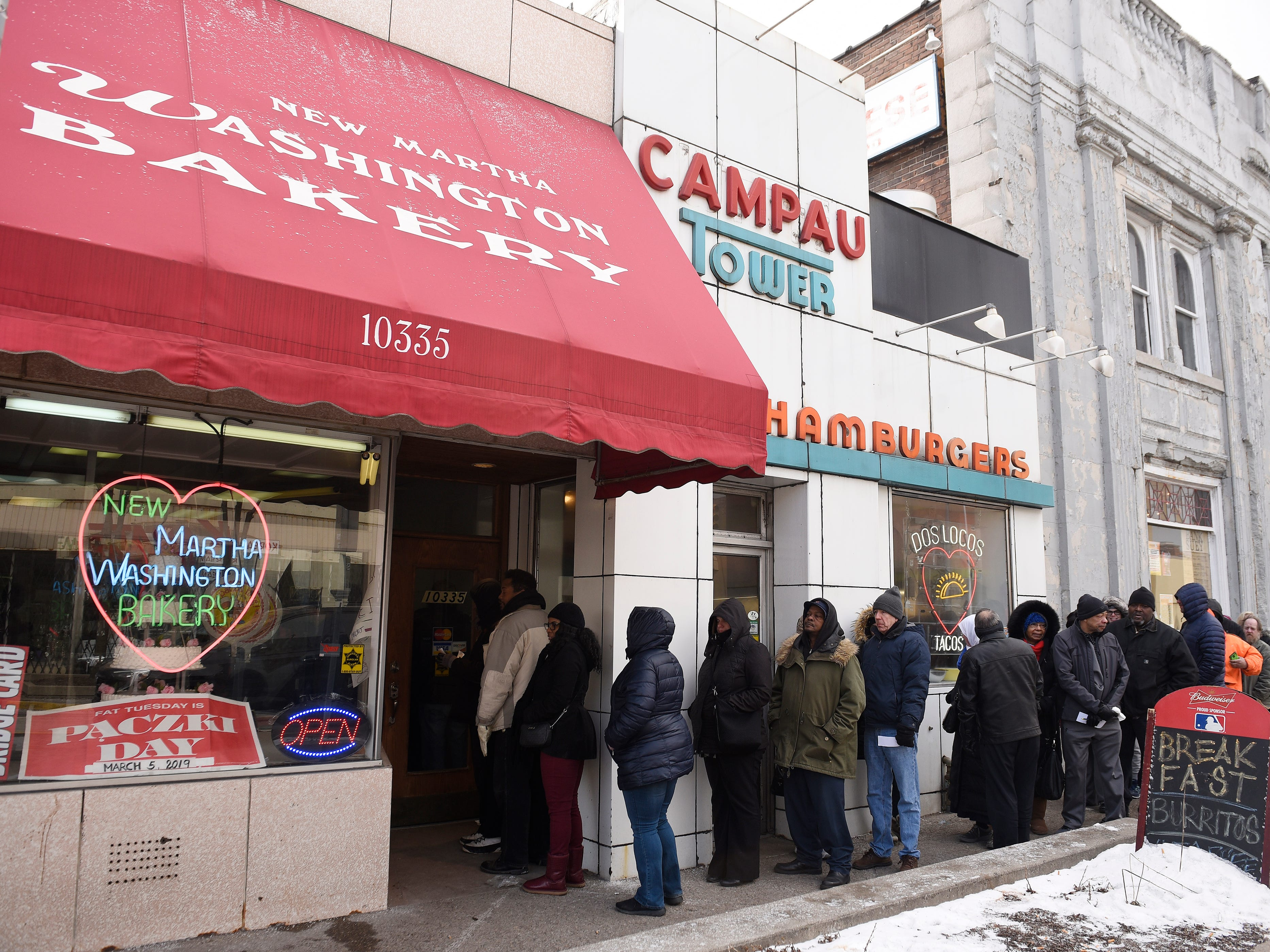 A long line of customers wait to enter the New Martha Washington Bakery to purchase their paczki.