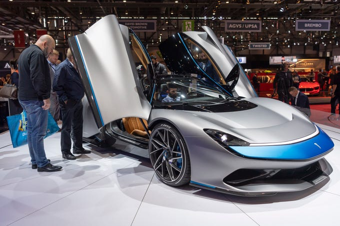 Visitors look at the new Automobili Pininfarina Battista during press day at the 89th Geneva International Motor Show in Geneva, Switzerland, Tuesday, March 5, 2019. The Geneva show takes place from March 7-17.