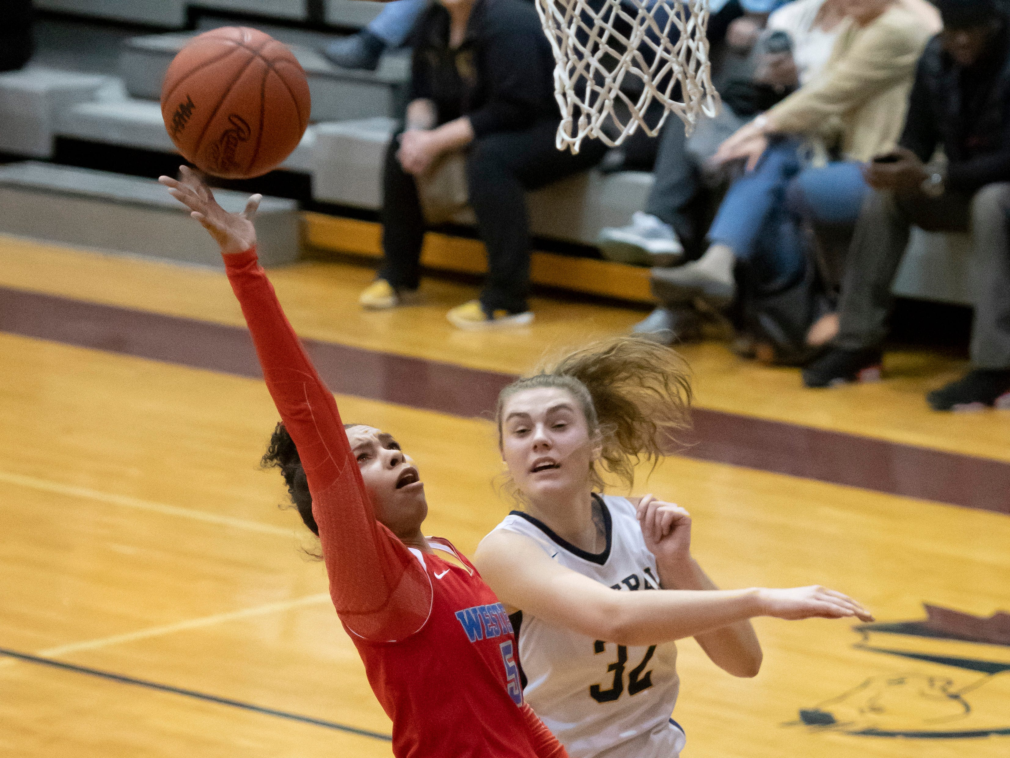 Walled Lake Western guard Kailee Ford takes a shot while being defended by Walled Lake Central's Olivia Emert in the second half.
