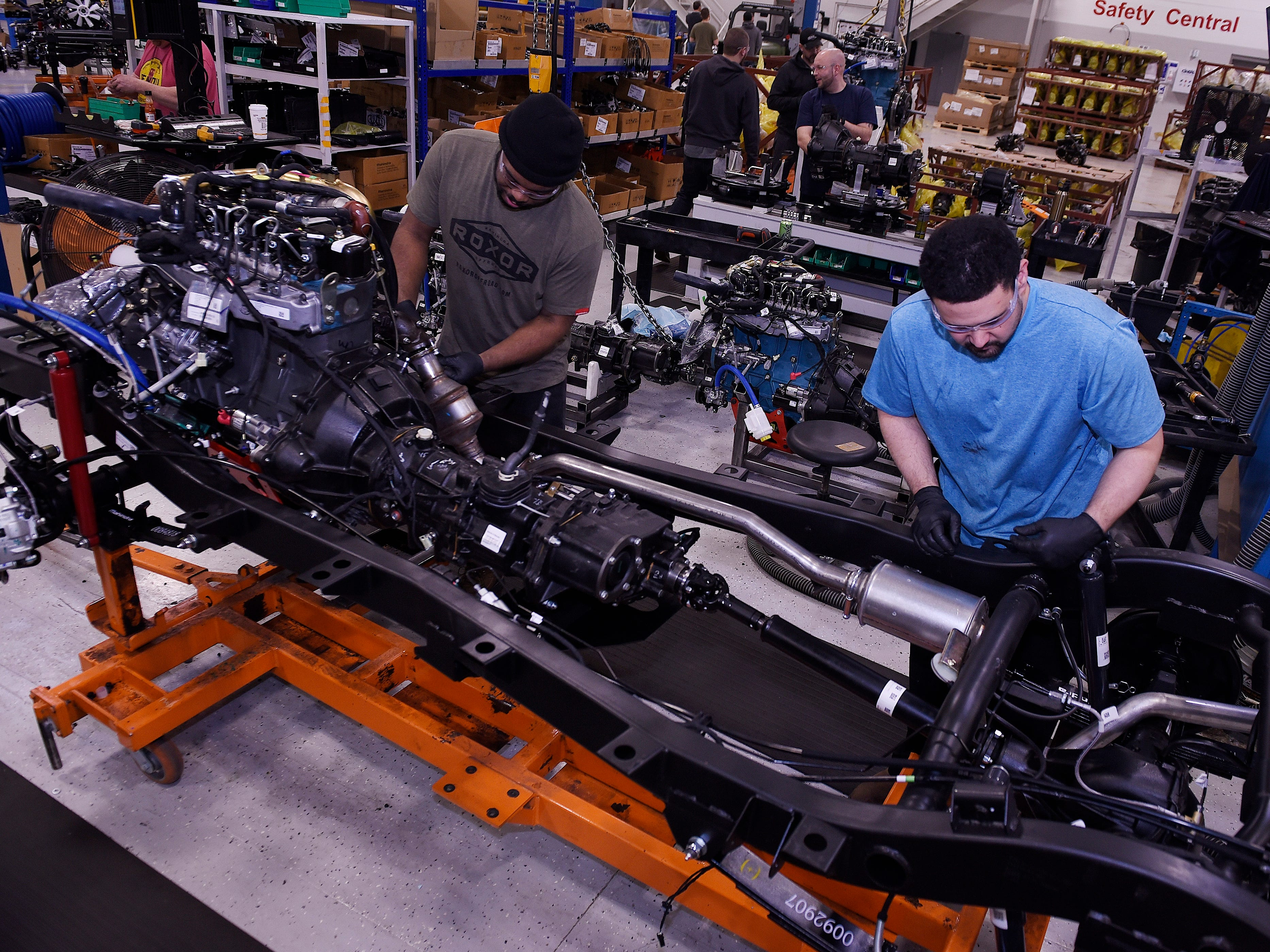 Terron Calmese, left, 38, and Doug Cortez, 32, install an engine in the chassis of an automobile at the Mahindra automotive plant in Auburn Hills, March 4, 2019.