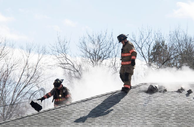 Evansville Fire Department firefighters Brian Stute, left, and Steve Bogard, right, work to clear a fire in the attic of a garage at 506 S. Bosse Ave. in Evansville, Ind., Tuesday, March 5, 2019.