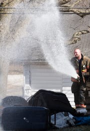 Evansville Fire Department firefighter Brian Stute sprays water on debris from the attic of a garage at 506 S. Bosse Ave. in Evansville, Ind., Tuesday, March 5, 2019.