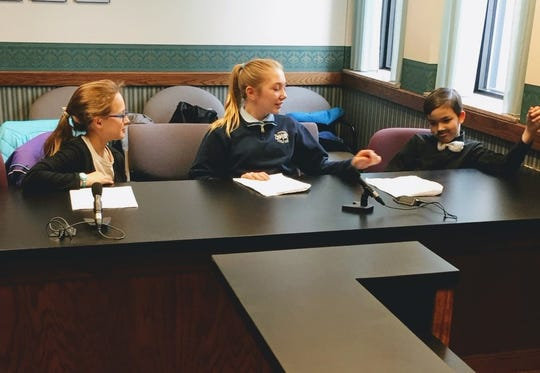 Jennifer Thompson, Cadance Ellenburg and Andrew Drill confer while waiting for the jury to return with a verdict. These fifth graders from St. Boniface Catholic School were players in the Mock Trial of B.B. Wolf vs. Curly Pig.