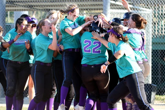 FSW softball players celebrate a home run by North Fort Myers graduate Natavia Ellis.