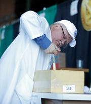 David Satterness of Chr. Hansen in South Dakota, pulls a sample of cheese Tuesday from an entry at the U.S. Championship Cheese Contest at Lambeau Field in Green Bay.