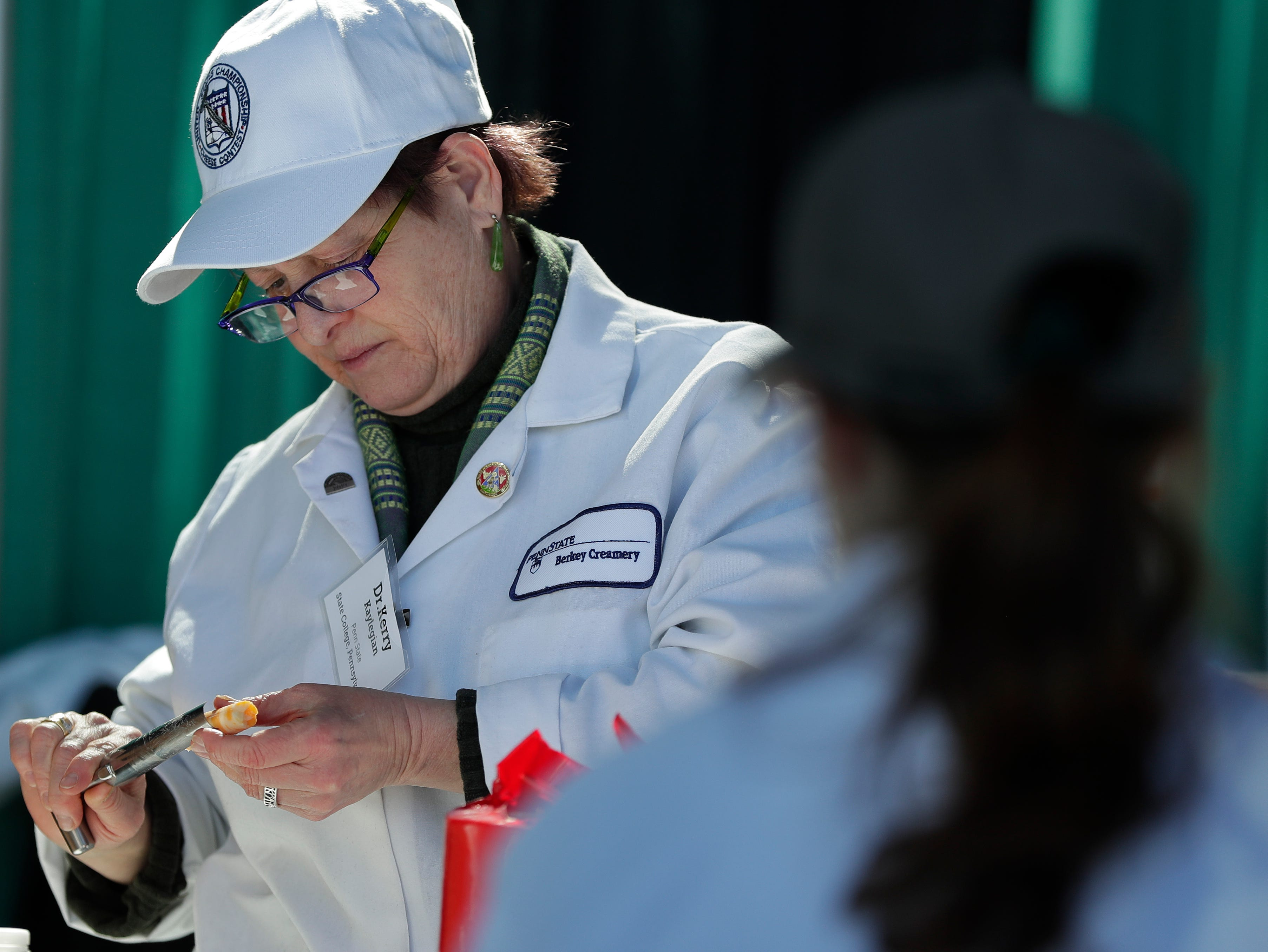 Dr. Kerry Kaylegian of Penn State University examines a piece of cheese at U.S. Championship Cheese Contest on March 5, 2019 at Lambeau Field in Green Bay, Wis.