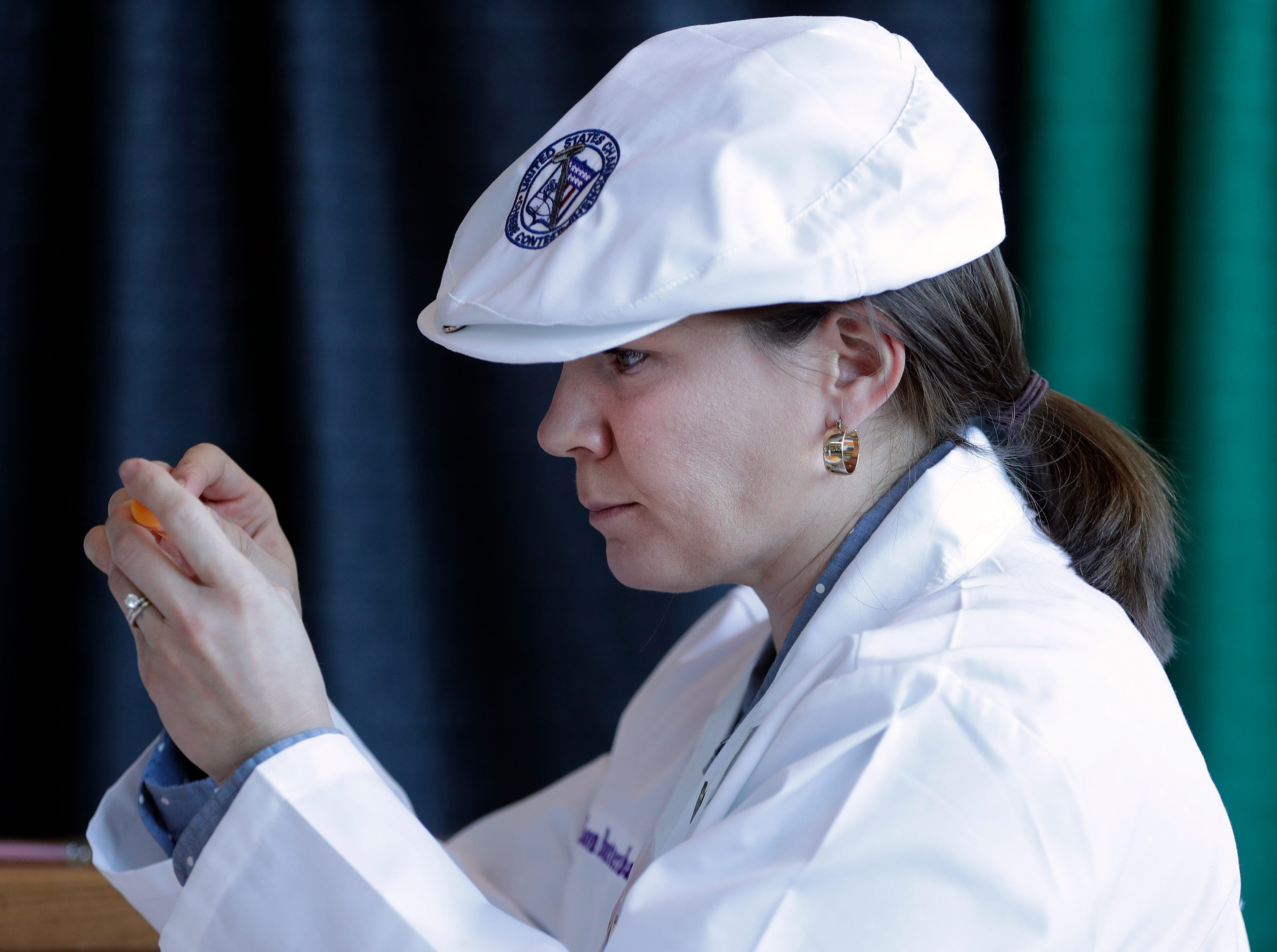 Allison Butterbaugh of Clemson University in South Carolina examines a piece of cheese at U.S. Championship Cheese Contest on March 5, 2019 at Lambeau Field in Green Bay, Wis.