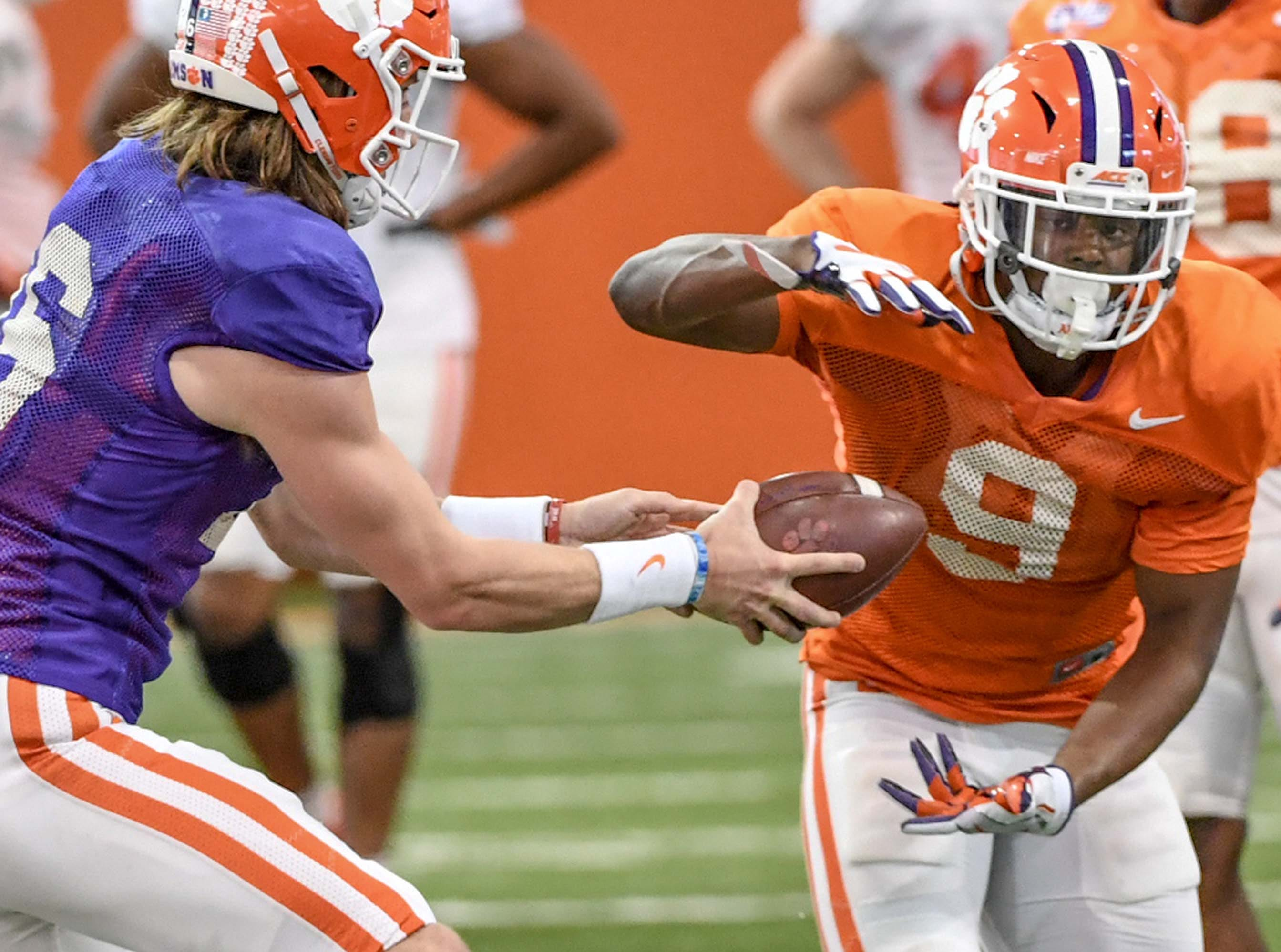 Clemson quarterback Trevor Lawrence (16) hands off to running back Travis Etienne (9) during practice at the Poe Indoor Facility in Clemson Monday.