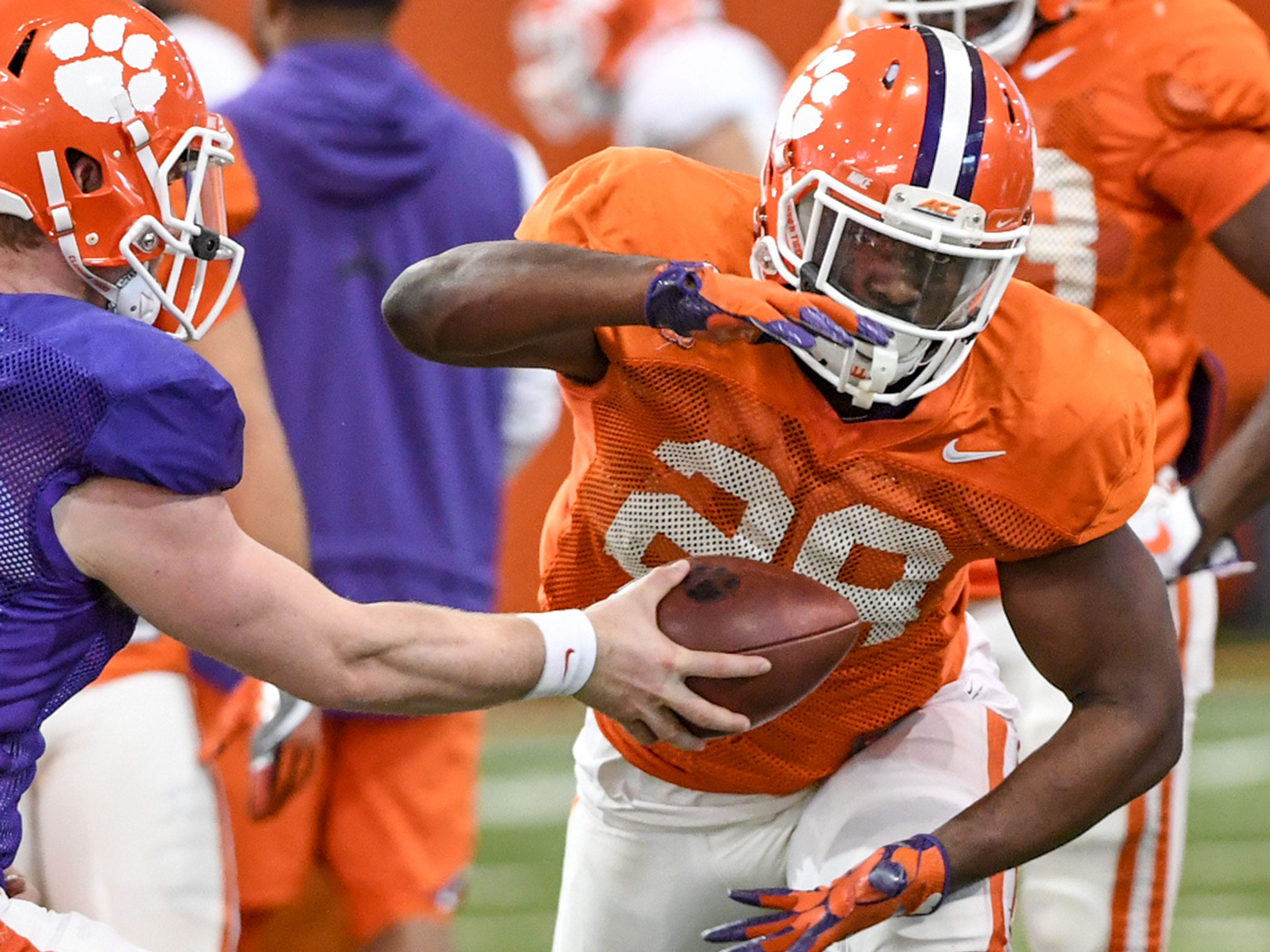 Clemson running back Tavien Feaster (28) takes a handoff in a drill during practice at the Poe Indoor Facility in Clemson Monday.