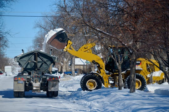 A work crew from Dr. Lawn removes a winters worth of snow from the C.M. Russell Museum parking lot on Tuesday morning.