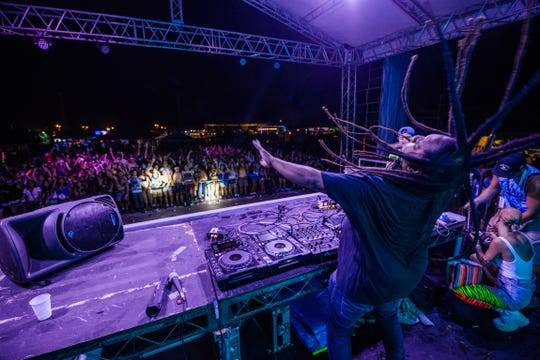 A DJ whips his dreadlocks on stage during an Electric Island Festival concert.