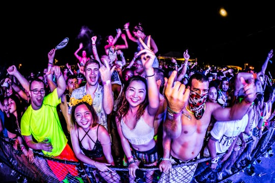 Concert goers line the fence in front of the stage during an Electric Island Festival concert.