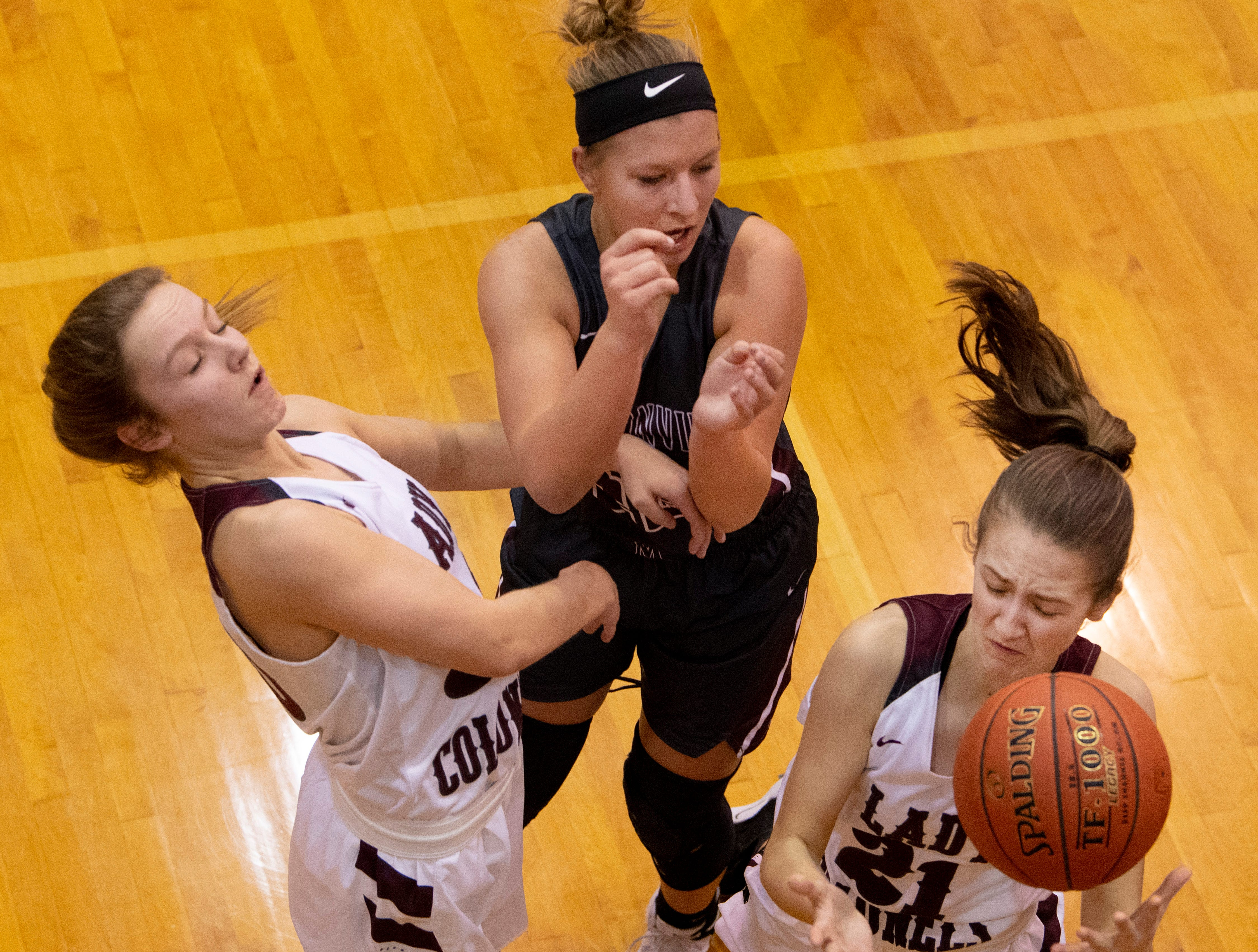Henderson County's Emilee Hope (30) and Henderson County's Graci Risely (21) go for a rebound against Madisonville's Camryn LaGrange (22) during the Girls Region Tournament semifinals at the Rocket Arena in Marion, Ky., Monday night.