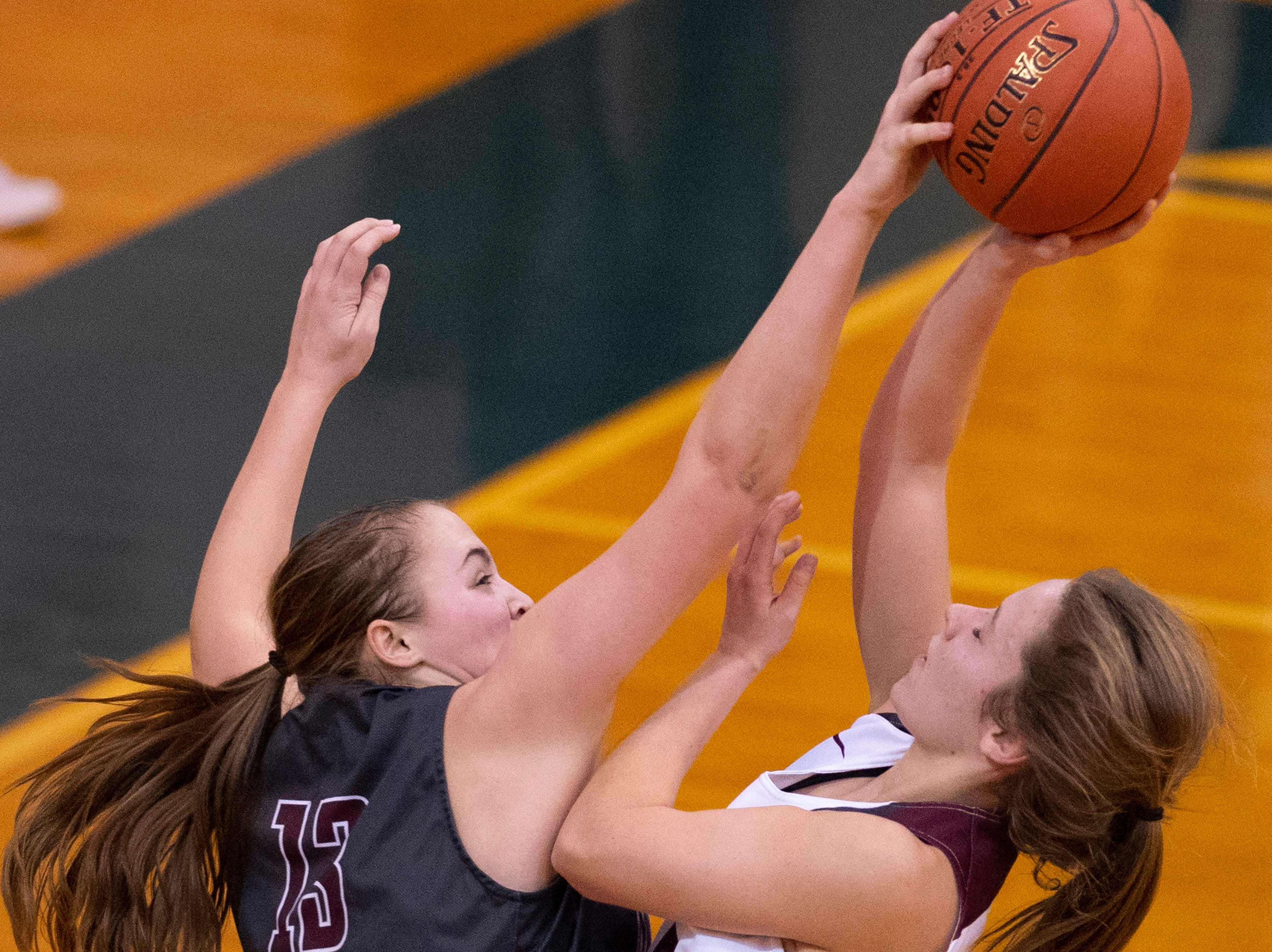 Madisonville's Kara Franklin (13) blocks the shot of Henderson County's Emilee Hope (30) during the Girls Region Tournament semifinals at the Rocket Arena in Marion, Ky., Monday night.