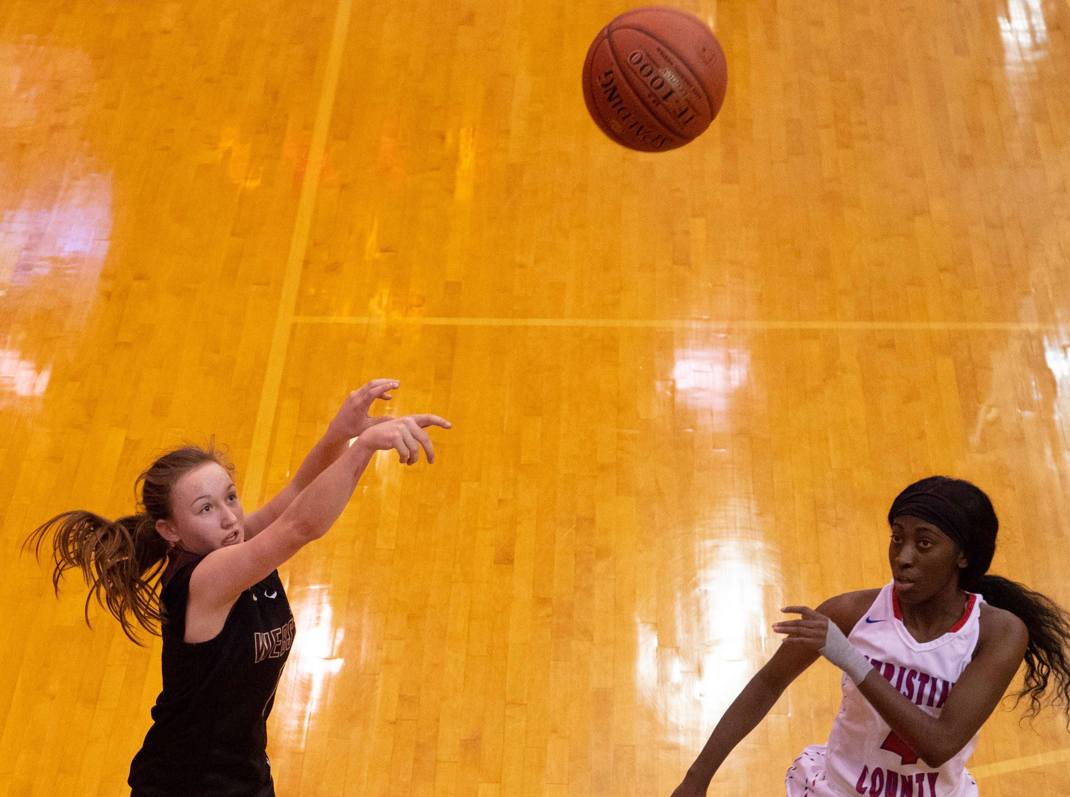 Webster County's Madison Hinton (12) shoots ahead of defender Christian's Kinara Phillips (4) during the Girls Region Tournament semifinals at the Rocket Arena in Marion, Ky., Monday night.