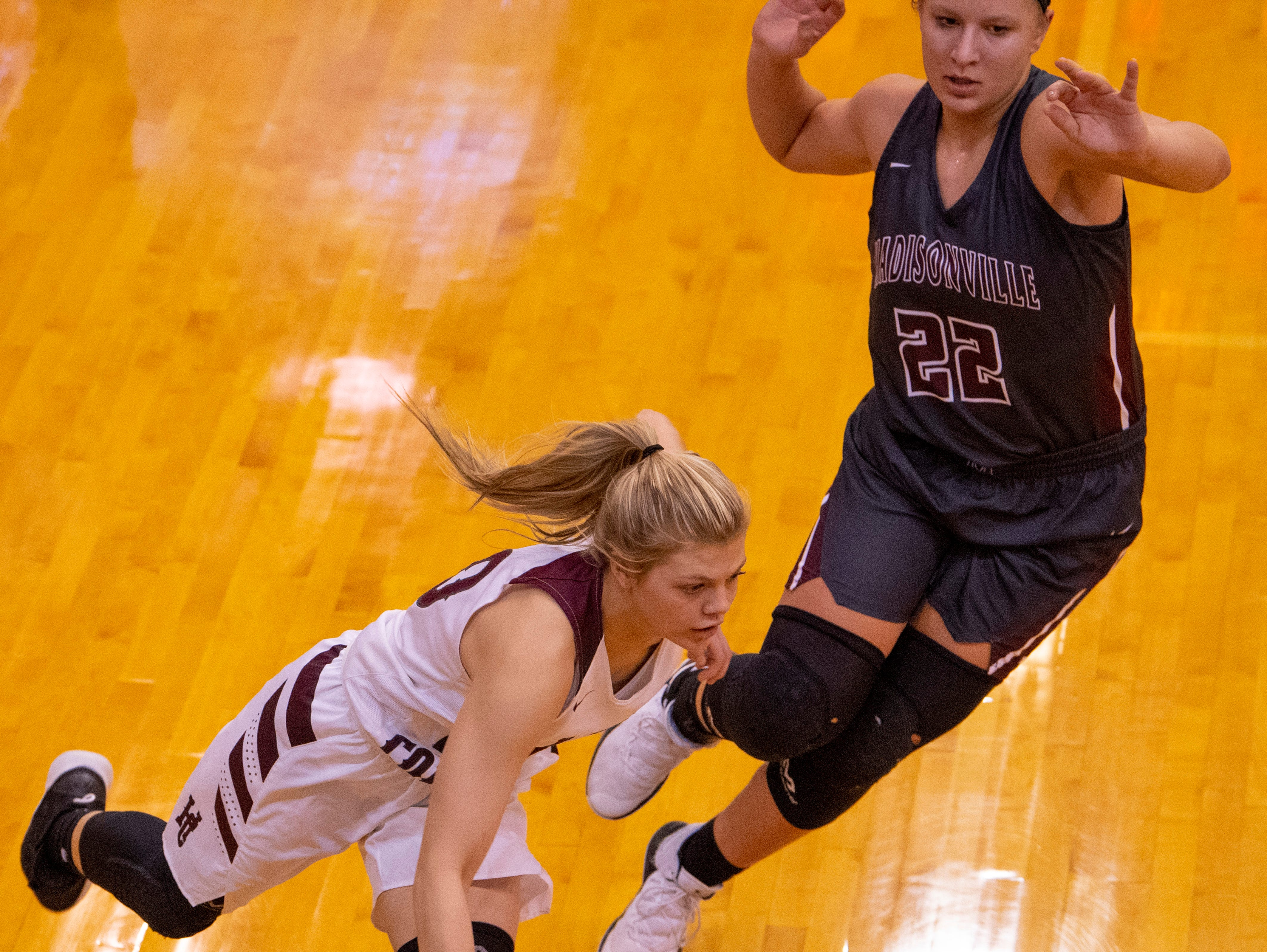 Henderson County's Kaytlan Kemp (20) drives past Madisonville's Camryn LaGrange (22) during the Girls Region Tournament semifinals at the Rocket Arena in Marion, Ky., Monday night.