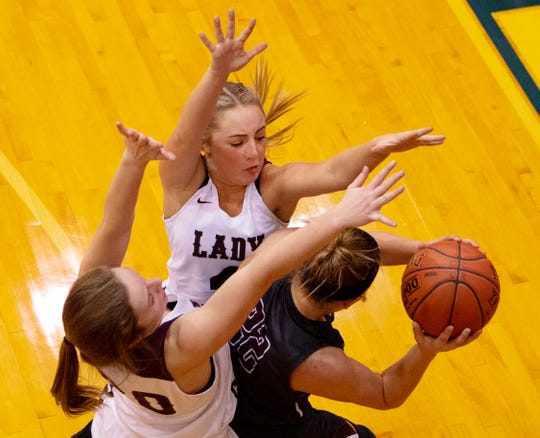 Henderson County's Savannah Lacer (4) and Henderson County's Emilee Hope (30) pressure Madisonville's Camryn LaGrange (22) during the Girls Region Tournament semifinals at the Rocket Arena in Marion, Ky., Monday night.