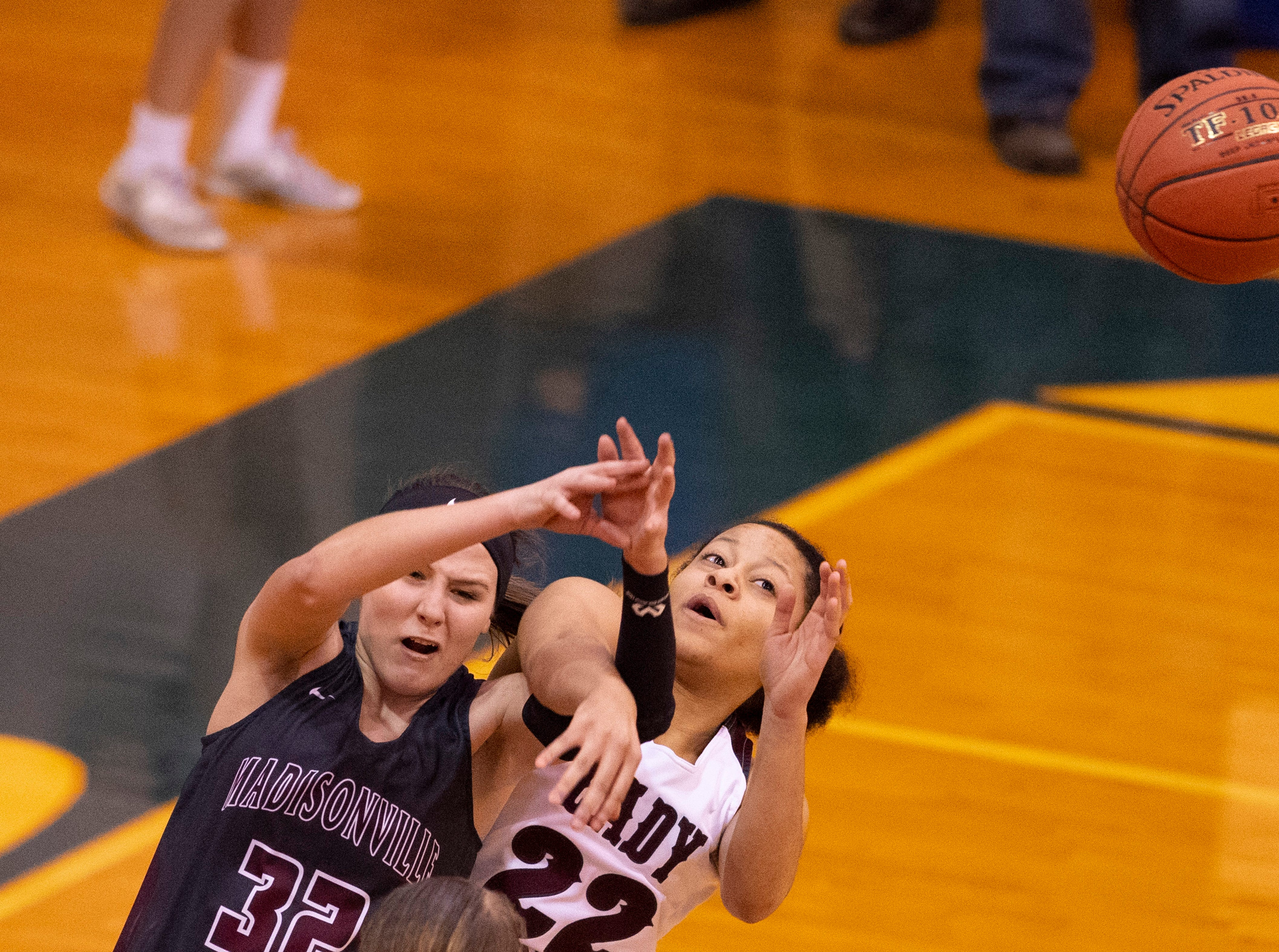 Madisonville's Lindsey Peyton (32) and Henderson County's Lauren Hubbard (22) fight for a rebound during the Girls Region Tournament semifinals at the Rocket Arena in Marion, Ky., Monday night.